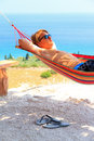 Hammock boy flipflops young man relaxing in a on the island of zakynthos greece Royalty Free Stock Image