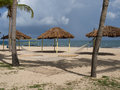 Hammock, Tiki Huts, and Volleyball Net on the Beach Royalty Free Stock Photo