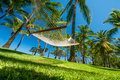 Hammock on tropical beach under palms and blue sky Stock Photo