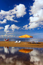 Hammock with an umbrella and chair on the beach with reflection chairs a narrow strip of beautiful of clouds in baltic sea Royalty Free Stock Image