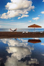 Hammock with an umbrella and chairs on a narrow strip of sand on beach beautiful reflection the clouds in the baltic sea Royalty Free Stock Photography