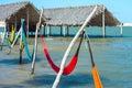 Hammocks under the shade of a palapa sun roof and beach chairs umbrella in jericoacoara brazil Royalty Free Stock Image