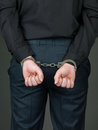 Hancuffed individual palmes closed back view of a person dressed in black with their hands behind their back and their palms Stock Images