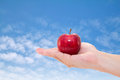 Hand with an apple isolated on sky Royalty Free Stock Photo