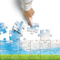 Hand assembling puzzle with beautiful landscape isolated in white background Royalty Free Stock Image