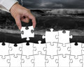 Hand assembling puzzle wall to change from tsunami to white Royalty Free Stock Photo