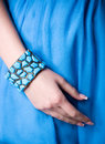 Hand in bangle on blue Royalty Free Stock Image
