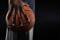Hand of basketball player holding a ball close up against black background Stock Images
