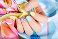 Hand with beautiful manicured nails holding colorful necklaces
