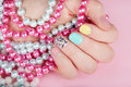 Hand with beautiful manicured nails holding colorful necklaces Royalty Free Stock Photo