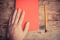 Hand with book and pencil resting on a red a next to it Stock Photo