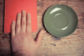 Hand with book and saucer at a table Royalty Free Stock Photography