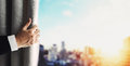 Hand of businessman opening curtain with blurred defocus panoramic Bangkok cityscape view in sunrise Royalty Free Stock Photo