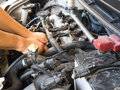 Hand of car mechanic working in auto repair service. He have fix old car engine