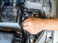 Hand of car mechanic working in auto repair service.