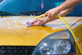 Hand car wash bonnet right side man washing his gold coloured using water hose and a cotton cloth Royalty Free Stock Photos
