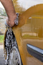 Hand car wash close up rear man washing his using water hose and a cotton cloth Stock Image