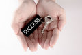 The hand carry the silver key with the label of success wording. Key to success concept isolated in white background Royalty Free Stock Photo