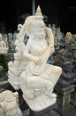 The hand-carved stone statue of the Hindu Goddess of Learning, Dewi Saraswati, plays the sitar Royalty Free Stock Photo