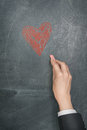 Hand with chalk drawing a heart on chalkboard Stock Photo