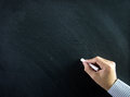 Hand on chalkboard close up of holding chalk blank Royalty Free Stock Image