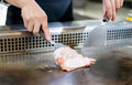 Hand of Chef cooking chicken steak on hot pan in front of custom Royalty Free Stock Photo