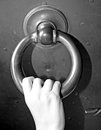Hand of a child who knocks on the door of an iron gate young Stock Image