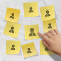 Hand choosing people icon on sticky note with crumpled paper as human resources concept Stock Photo