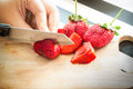 Hand chopping a fresh strawberry in kitchen Royalty Free Stock Images