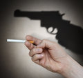 Hand with a cigarette and gun Stock Image