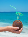 Hand with coconut drink made by the shore Royalty Free Stock Images