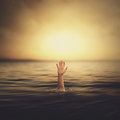 A hand coming out of the water up looking for help Royalty Free Stock Photos