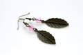 Hand crafted earrings made with metal leaves and pink crystals isolated on the white background Stock Photos