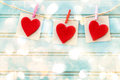 Hand crafted felt hearts hanging with clothespins over shiny wooden board Stock Photo