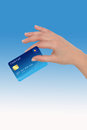 Hand with credit card female holding a on blue background Royalty Free Stock Photo