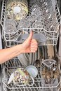 Hand and dishwasher with clean dishes Royalty Free Stock Photo