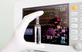Hand of doctor holding medicine against heart monitor Stock Images