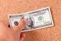 Hand and dollar bill one hundred on cork bulletin board Royalty Free Stock Image