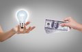 Hand with dollars and light bulb on gray background Royalty Free Stock Images