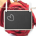 Hand drawing heart on blackboard with dry red rose background, i Royalty Free Stock Photo