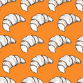 Hand drawn fresh baked croissant seamless pattern on orange background.