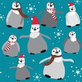 Penguins with christmas hats and scarfs with snowflakes seamless pattern. Vector illustration on blue background Royalty Free Stock Photo