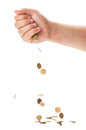 Hand dropping a bunch of golden coins on white table Royalty Free Stock Photography