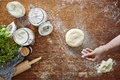 Hand dusting dough with flour wooden kitchen surface Royalty Free Stock Photo