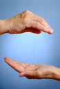 Hand of elderly woman above young woman s hand on blue background Royalty Free Stock Photos