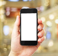 Hand with empty cell phone on blurred background Royalty Free Stock Photo