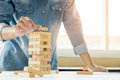 Hand of engineer playing a blocks wood tower game & x28;jenga& x29; on blu Royalty Free Stock Photo