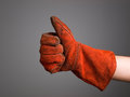 Hand expressing positivity with welder glove isolated on dark background Royalty Free Stock Images