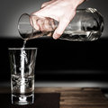 Hand fills in water with glass jug on wooden table Royalty Free Stock Photography