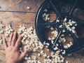 Hand with film reel and popcorn Royalty Free Stock Photo